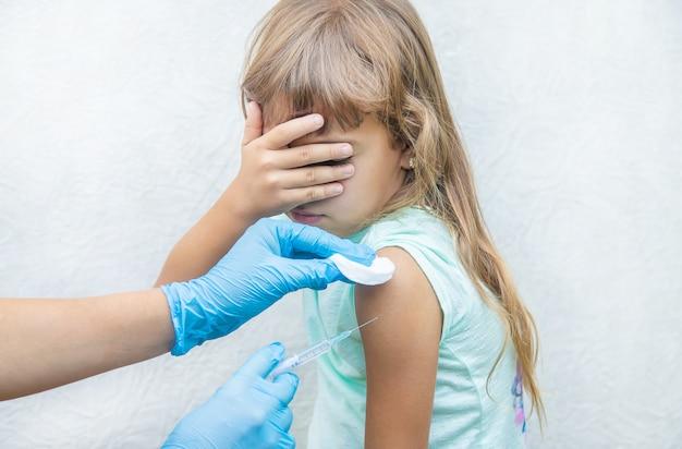 Il medico fa al bambino un'iniezione nel braccio