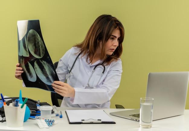 Il medico femminile di mezza età di pensiero che porta veste medica con lo stetoscopio che si siede allo scrittorio funziona sul computer portatile con gli strumenti medici che tengono i raggi x e che esamina il computer portatile sulla parete verde