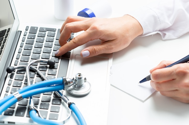 Il medico femminile sta scrivendo in computer portatile