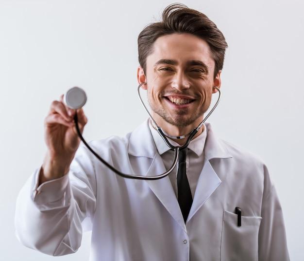 Il medico in abito bianco e stetoscopio sta sorridendo.