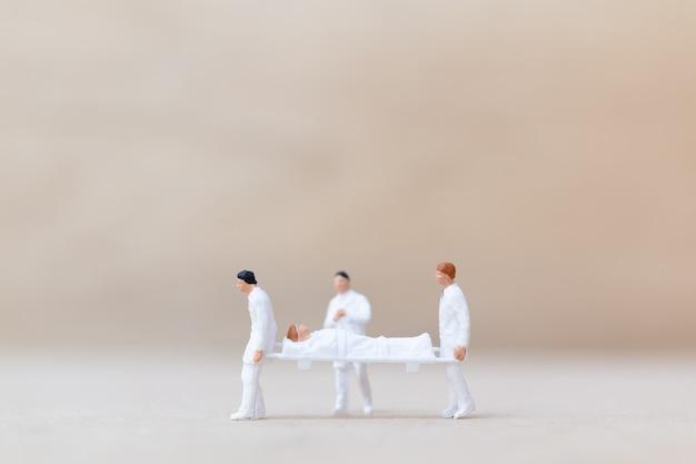 Il medico in miniatura con l'infermiera trasporta il paziente su una barella