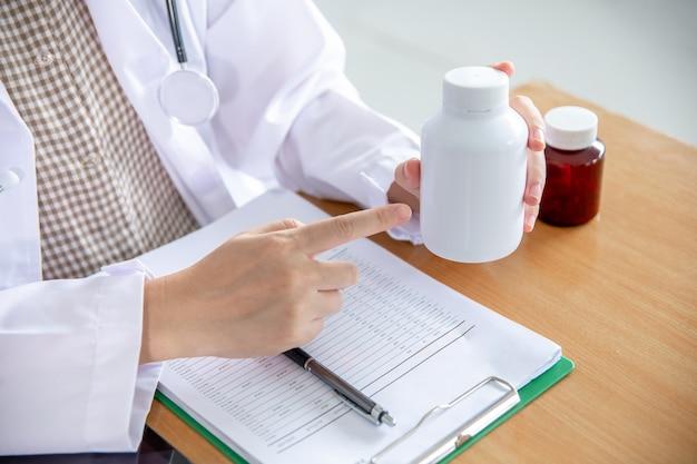 Il medico indicò il dito per introdurre la bottiglia di medicina al paziente.