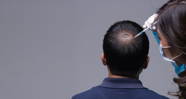 Il medico inietta il trattamento delle vitamine del siero caduta dei capelli