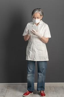 Il medico lavora con computer tablet. la donna matura seria in uniforme e maschera usa la compressa digitale che sta a tutta altezza in ufficio medico