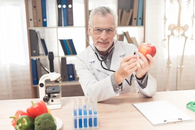 Il medico maschio sta ascoltando apple con lo stetoscopio