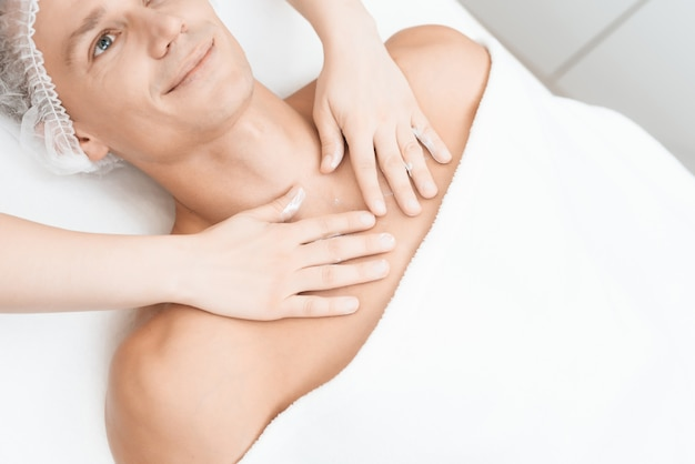 Il medico massaggia e spalma la crema sul viso
