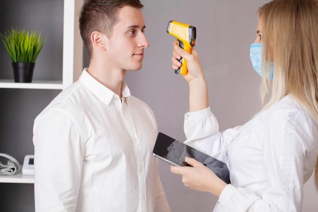 Il medico misura la temperatura del paziente con un termometro laser