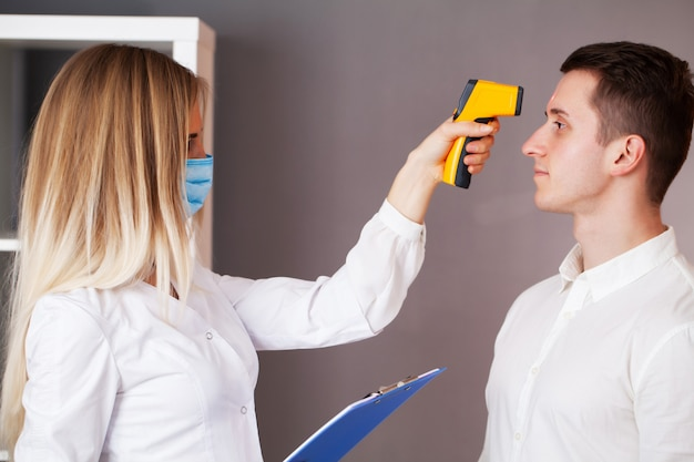 Il medico misura la temperatura di un paziente durante un'epidemia covid-19