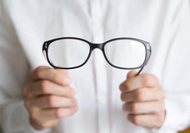 Il medico oculista sta tenendo gli occhiali. il concetto di problemi di vista. concetto ottico.
