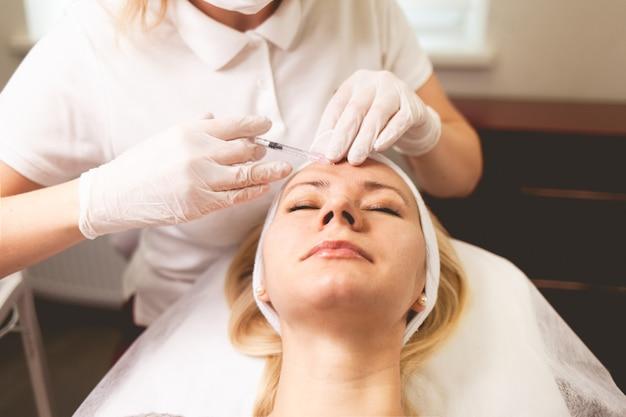 Il medico osmetologo inietta il botox nella fronte del paziente