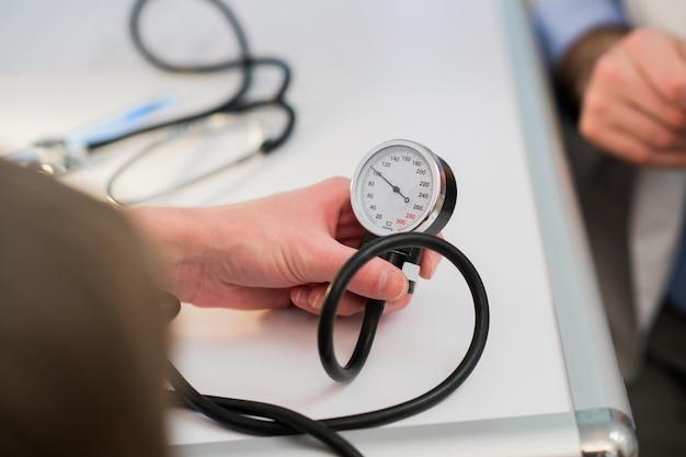 Il medico sta misurando la pressione sanguigna con un tonometro