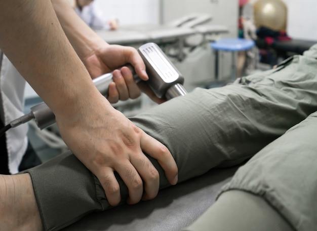 Il medico sta riabilitando le gambe del paziente