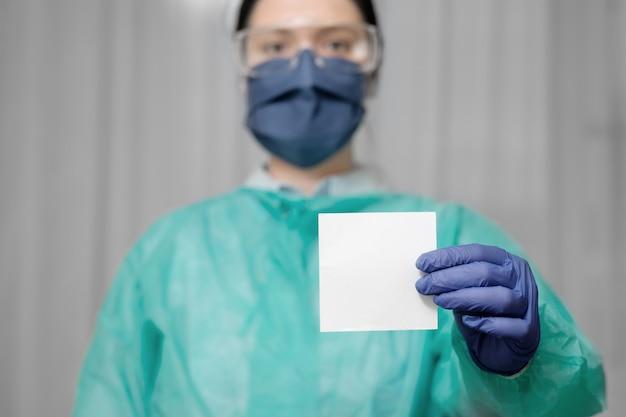 Il medico tiene in mano un pezzo di carta per il testo, resta a casa, fa appello al dottore nell'epidemia di coronavirus