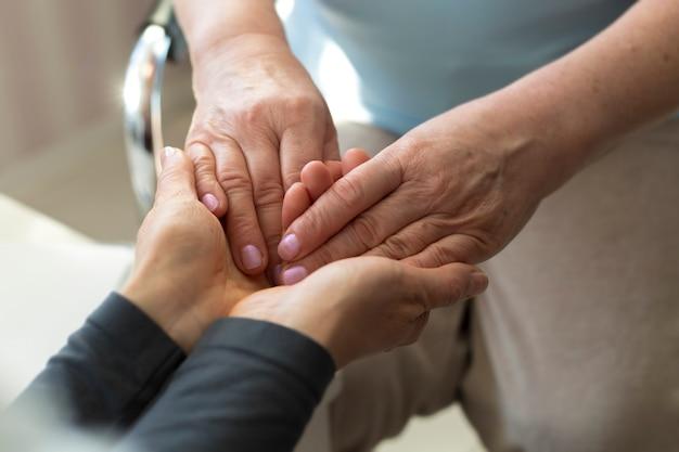 Il medico tiene la mano di una donna anziana