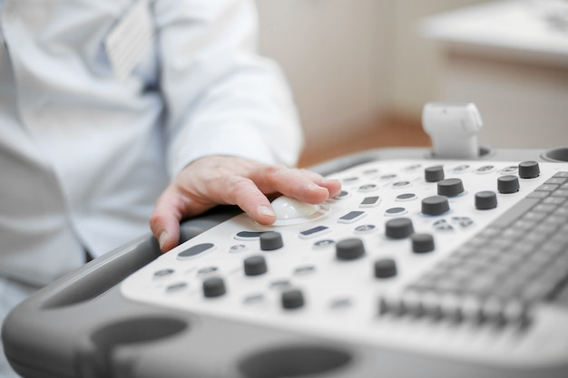 Il medico tiene un'ecografia sul paziente, una mano da vicino