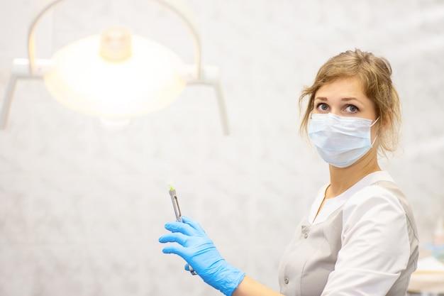 Il medico tiene una siringa e si sta preparando a fare un'iniezione in una clinica medica
