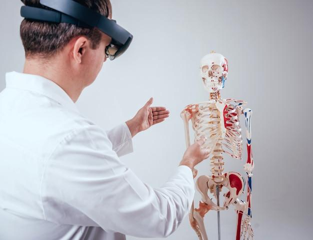 Il medico usa occhiali di realtà aumentata per esaminare lo scheletro umano