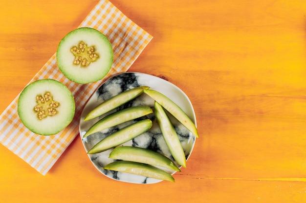 Il melone si sbuccia in un piatto bianco con diviso nella vista superiore del mezzo melone su un fondo arancio