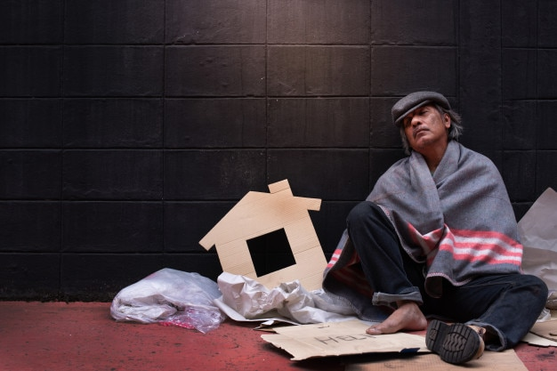 Il mendicante si appoggia al muro con fatica sotto la coperta