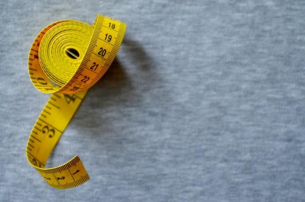 Il metro a nastro giallo si trova su un tessuto a maglia grigia