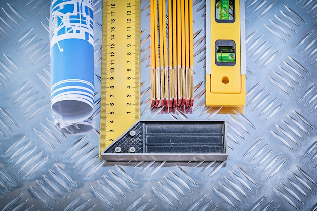 Il metro di legno livellato dei disegni di costruzione prova il quadrato sul fondo scanalato del metallo