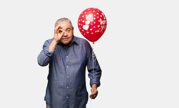 Il mezzo ha invecchiato l'uomo che celebra il giorno di biglietti di s. valentino sicuro che fa gesto giusto sull'occhio