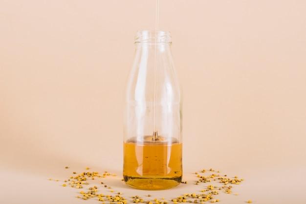 Il miele che gocciola in bottiglia di vetro con il polline dell'ape su pesca ha colorato il fondo