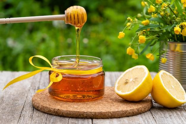Il miele fresco scorre nel barattolo.