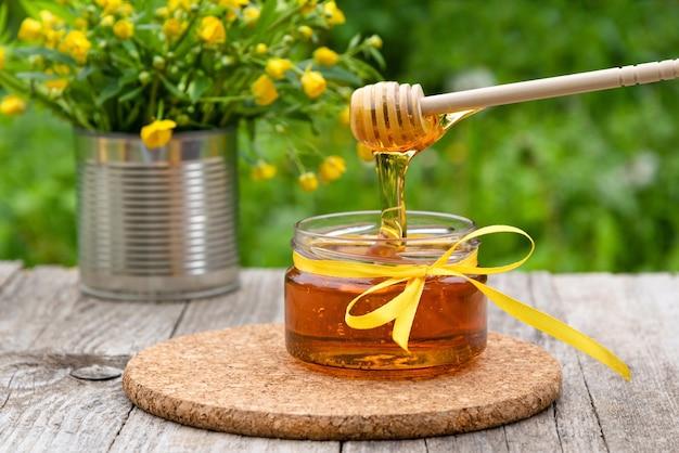 Il miele gocciola dal cucchiaio nel barattolo
