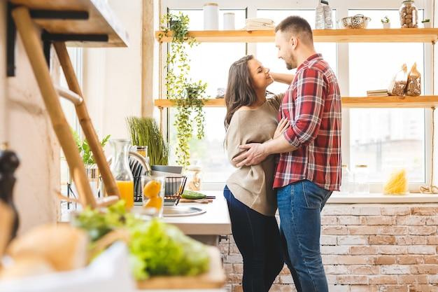 Il miglior tempo libero è rilassarsi a casa insieme. belle giovani coppie che cucinano cena mentre stando nella cucina a casa.