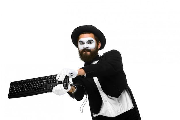 Il mimo arrabbiato come uomo d'affari sta distruggendo la tastiera