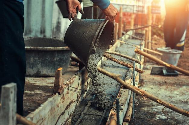 Il miscelatore del lavoratore versa il cemento della costruzione sul pavimento per la casa della costruzione