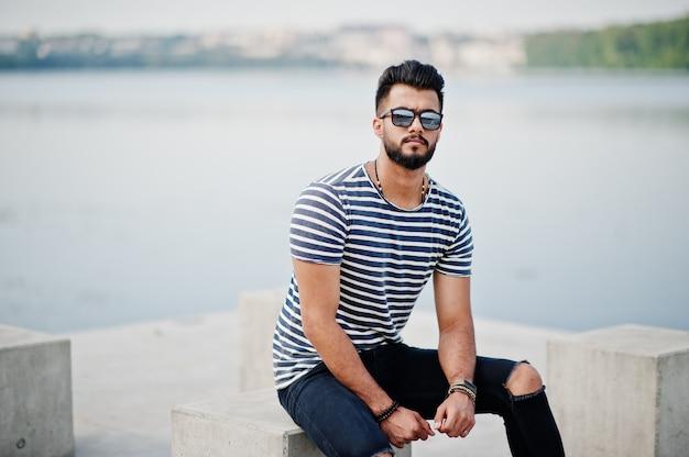 Il modello arabo alto bello dell'uomo della barba alla camicia spogliata ha posato all'aperto. ragazzo arabo alla moda agli occhiali da sole.