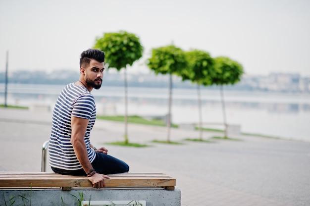 Il modello arabo alto bello dell'uomo della barba alla camicia spogliata ha posato all'aperto. ragazzo arabo alla moda.