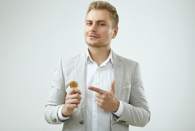 Il modello bello biondo dell'uomo in un vestito grigio di modo tiene un bitcoin