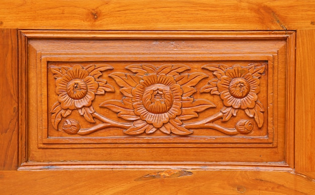 Il modello del fiore ha scolpito su fondo di legno, stile tailandese