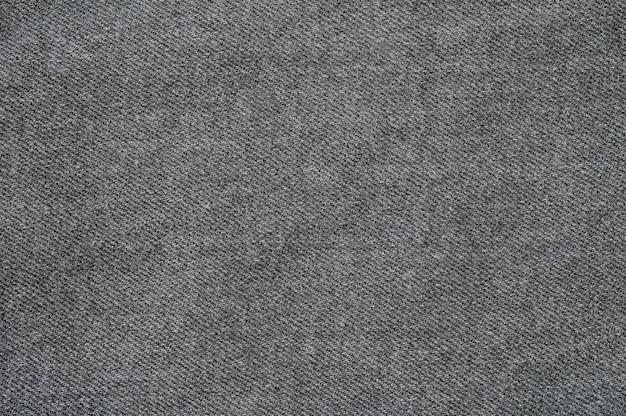 Il modello del tessuto della superficie del primo piano ai vecchi pantaloni neri del tessuto ha strutturato il fondo