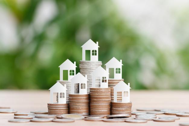 Il modello della casa sulla pila delle monete per il risparmio per comprare una casa