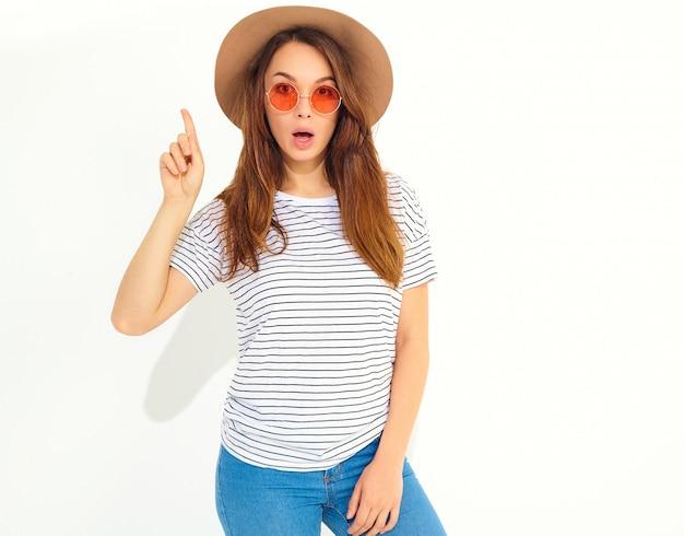 Il modello di giovane donna alla moda in abiti estivi casual in cappello marrone ha una buona idea in mente