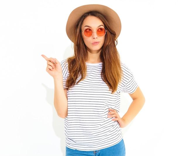 Il modello di giovane donna elegante in abiti estivi casual in cappello marrone ha una buona idea in mente come migliorare il progetto, alza il dito, vuole suonare ed esprimere pensieri, ha un'espressione preoccupata isolata sulla pentecoste