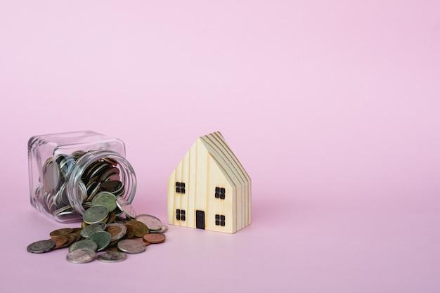 Il modello di legno della casa con soldi conia nel barattolo di vetro su fondo rosa con lo spazio della copia per l'affare e la finanza per il concetto della proprietà