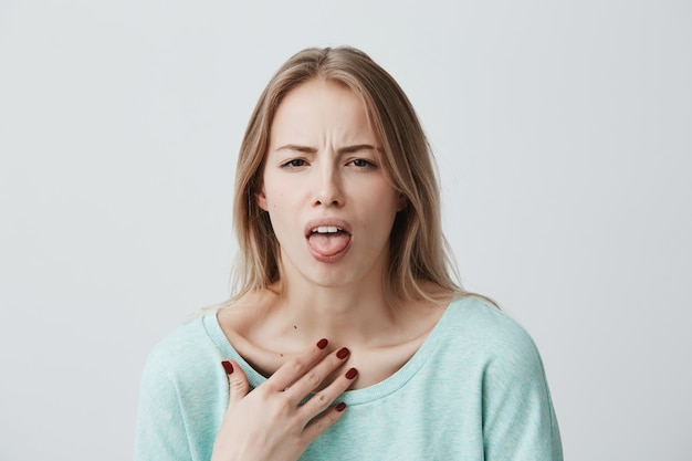 Il modello femminile biondo insoddisfatto aggrotta la fronte, ha un'espressione disgustosa, mostra la lingua, esprime non conformità, irritato con qualcuno, gli scarti fanno qualcosa. persone ed espressioni facciali negative