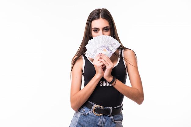 Il modello femminile castana tenero in brevi blue jeans tiene il fan delle banconote in dollari