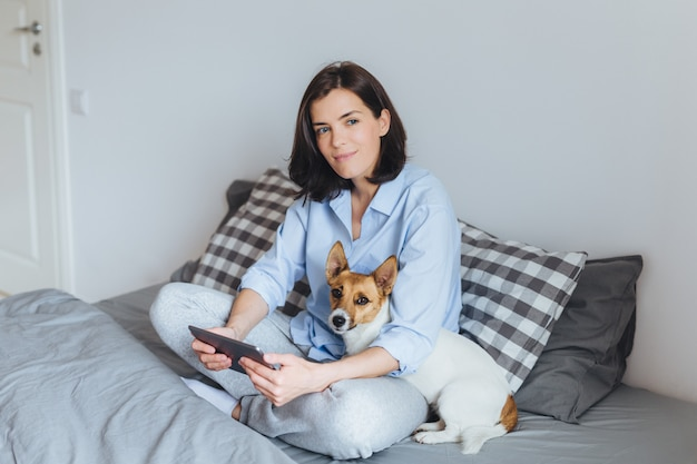 Il modello femminile castana vago in pigiama si siede le gambe attraversate sul letto comodo in camera da letto, tiene la compressa moderna, abbraccia il suo animale domestico