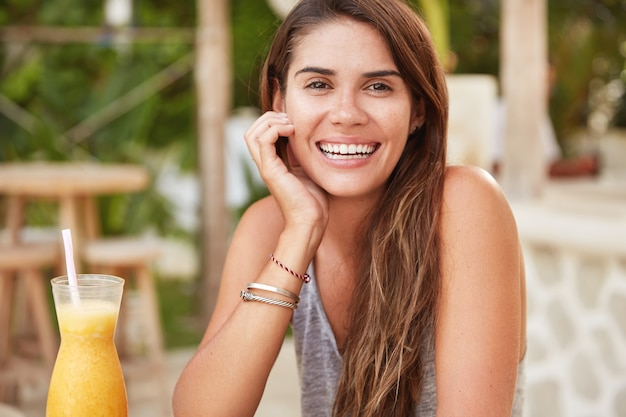Il modello femminile soddisfatto con un ampio sorriso affascinante si rallegra delle vacanze estive nel paese del resort, beve cocktail analcolici freschi