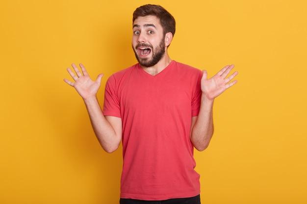 Il modello maschio barbuto caucasico scosso e confuso veste l'attrezzatura casuale che sta con le palme spante e la bocca aperta