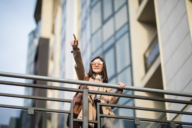 Il modello tenero del brunette cammina sul ponticello moderno nel centro urbano