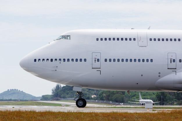 Il moderno aereo passeggeri a due piani è in rullaggio per decollare. velivoli wide-body sulla pista, fine in su, vista laterale.