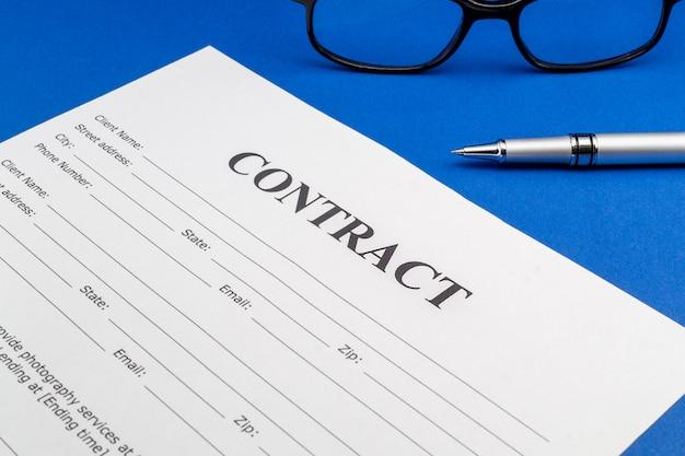 Il modulo di contratto sul tavolo e sulla penna blu