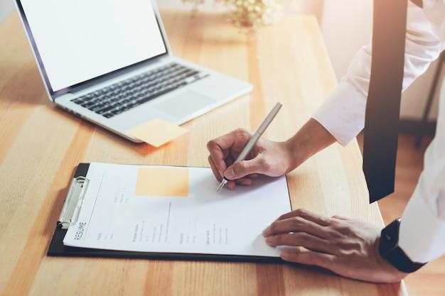 Il modulo di scrittura di un uomo d'affari invia il datore di lavoro per la revisione della domanda di lavoro.